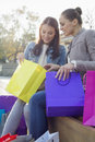 Beautiful woman with friend looking into shopping bag outdoors Royalty Free Stock Photo