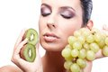 Beautiful woman with fruits eyes closed artistic photo of young holding grapes and kiwifruit in hand Stock Photos