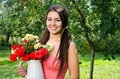 Beautiful woman in the garden with flowers girl smiling holding a vase a bouquet of red and yellow roses on a hot summer day Royalty Free Stock Image