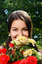 Beautiful woman in the garden smelling flowers girl a bouquet of red and yellow roses on a hot summer day Stock Photos