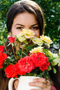 Beautiful woman in the garden smelling flowers girl a bouquet of red and yellow roses on a hot summer day Royalty Free Stock Photo