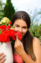 Beautiful woman in the garden smelling flowers girl a bouquet of red and yellow roses on a hot summer day Royalty Free Stock Image