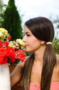 Beautiful woman in the garden smelling flowers girl a bouquet of red and yellow roses on a hot summer day Stock Images