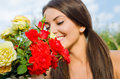 Beautiful woman in the garden smelling flowers girl a bouquet of red and yellow roses on a hot summer day focus on blur on girl Royalty Free Stock Photo