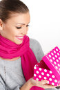 Beautiful woman a gift from a loved one for the holiday portrait of young in pink scarf with pink lipstick holding pink box in Stock Photo