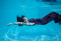 Beautiful woman girl dress underwater diving swim blue sunny day pool Royalty Free Stock Photo
