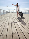 Beautiful woman girl sea mooring suitcase on a pier going Stock Photos