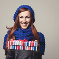 Beautiful woman giving a colourful christmas gift young redhead in warm woolly blue knitted winter scarf and cap with lovely Stock Photography