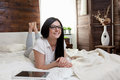 Beautiful woman with glasses relaxing on the bed and using her tablet Royalty Free Stock Photo