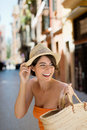 Beautiful woman going out shopping in a trendy summer dress and straw hat looking back expectantly over her shoulder with a smile Stock Image