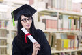 Beautiful woman in graduation gown pose at library with glasses posing the wearing Stock Photo