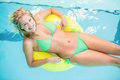 Beautiful woman in green bikini relaxing on inflatable tube in swimming pool Royalty Free Stock Photo