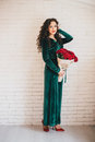 Beautiful woman in a green dress and red shoes with red roses velvet velvet bouquet Royalty Free Stock Photography