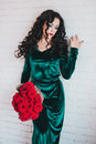 Beautiful woman in a green dress and red shoes with red roses velvet velvet bouquet Royalty Free Stock Photos