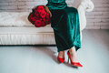 Beautiful woman in a green dress and red shoes with red roses velvet velvet bouquet Royalty Free Stock Image