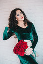 Beautiful woman in a green dress and red shoes with red roses velvet velvet bouquet Royalty Free Stock Images