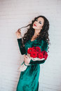 Beautiful woman in a green dress and red shoes with red roses velvet velvet bouquet Stock Photography