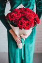 Beautiful woman in a green dress and red shoes with red roses velvet velvet bouquet Stock Images