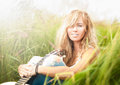 Beautiful woman with guitar sitting on grass. Royalty Free Stock Photo