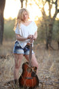Beautiful woman and guitar vertical image of a blond holding an acoustic at sunset Royalty Free Stock Images
