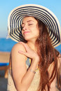 Beautiful woman in hat enjoying on the beach under blue sky closeup portrait Royalty Free Stock Images