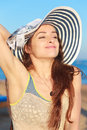 Beautiful woman in hat enjoying on the beach under blue sky and sea background Stock Photo