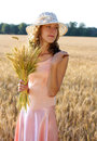 Beautiful woman in the hat holding wheat ears in her hand against a background of field concept of abundance Royalty Free Stock Photo