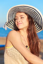 Beautiful woman in hat joying sunny summer day and looking on sea background Royalty Free Stock Photos