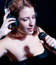 Beautiful  woman with headphones and mic singing Stock Images