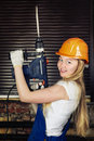 Beautiful woman with heavy drill blond in his hand Stock Photography