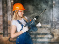 Beautiful woman with heavy drill blond in his hand Royalty Free Stock Photography