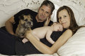 Beautiful woman her husband newborn baby and dog a father sits with a mother who cuddles new born sits with pet while the sleeps Royalty Free Stock Photos