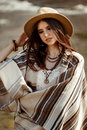 Beautiful woman hipster portrait, holding hat and poncho, stylish outfit, boho travel concept, sensual look