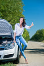 Beautiful woman hitchhiking by a broken car Stock Photo