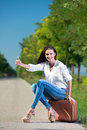 Beautiful woman hitchhiking with suitcase Royalty Free Stock Photography