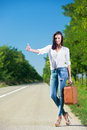Beautiful woman hitchhiking with suitcase Stock Photo