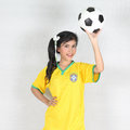 Beautiful woman hold ball over her head with wearing Brazil foot Royalty Free Stock Photo