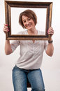 Beautiful woman holding around her face a frame and looking thro through Royalty Free Stock Photography