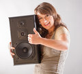 Beautiful woman holding big wooden speaker young with closed eyes and listening music Royalty Free Stock Images