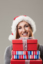 Beautiful woman holding christmas presents young in a festive red furry santa hat a pile of colourful and gift boxes on a grey Stock Photos