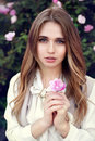 Beautiful woman holding a flower outdoors and looking in camera Royalty Free Stock Photo