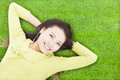 Beautiful woman holding head and lying on a meadow Royalty Free Stock Photos