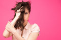 Beautiful woman holding her hair over pink background covering half face with looking at camera Stock Images