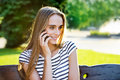 Beautiful woman holding mobile phone in hand and sitting on the bench young park Royalty Free Stock Photo