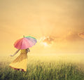 Beautiful woman holding multicolored umbrella in green grass fie
