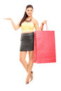 Beautiful woman holding shopping bags and gesturing with her han full length portrait of a hand isolated on white background Stock Images