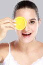 A beautiful woman holding a slice of fresh lemon Royalty Free Stock Photo
