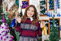 Beautiful woman holding small shopping bags in portrait of young at christmas store Stock Images