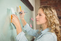 Beautiful woman holding sticky note while writing on glass board Royalty Free Stock Photo