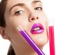 Beautiful woman holding two test tubes different color liquid as well as her lips Royalty Free Stock Photography